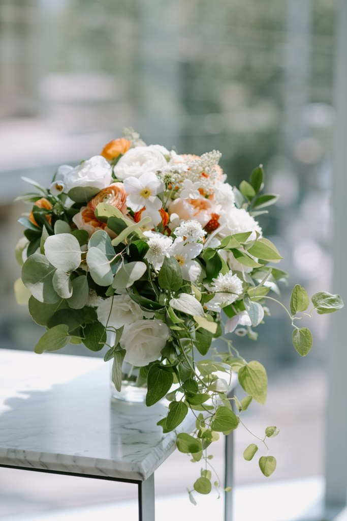 Wild and loose white, orange, and green wedding bouquet. Click for more modern and minimal wedding design from this rooftop wedding at The Thompson Hotel in Seattle, WA. Wedding planning by Perfectly Posh Events, based in Seattle and Portland. Wedding photography by Kristen Marie Parker Photography. Wedding bouquet by Sublime Stems. #perfectlyposhevents