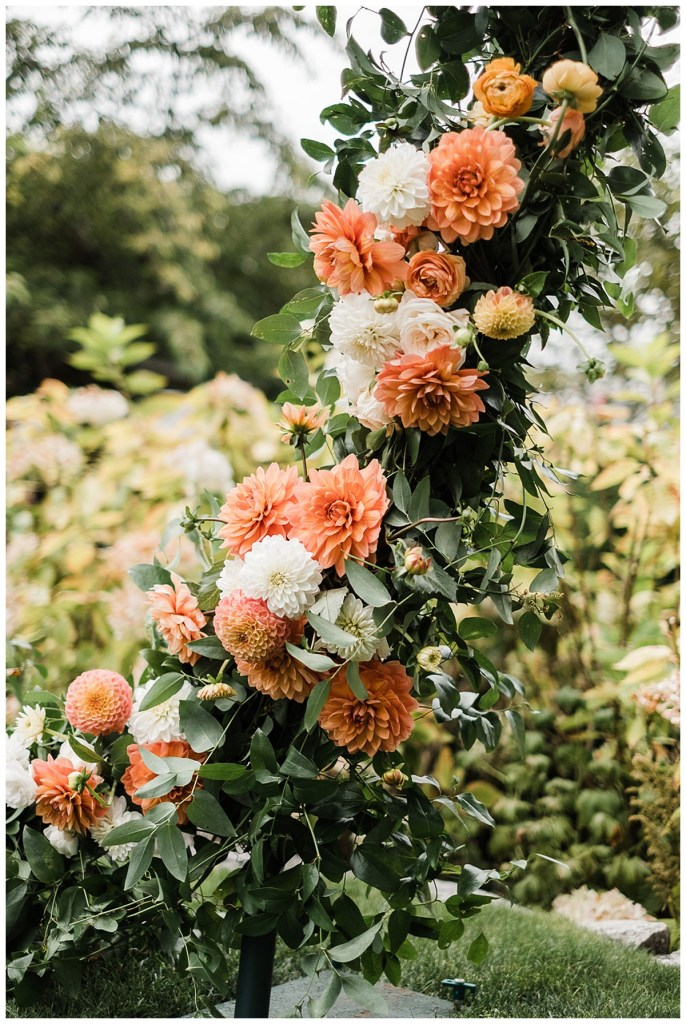 Orange and yellow and white wedding flowers with greenery for wedding ceremony arch.