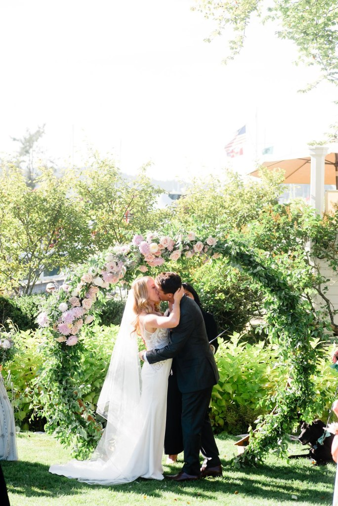 Roche Harbor Resort ceremony with lush green circle arch and pale pink and purple flowers.Click for more neutral and pastel chic wedding design from this San Juan Island wedding at Roche Harbor Resort in San Juan Island, WA. Wedding planning by Perfectly Posh Events, based in Seattle and Portland. Wedding photography by Lloyd Photographers. Flowers by Bloom San Juan. #perfectlyposhevents