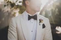 The Foundry by Herban Feast wedding in Seattle | Mid-century modern groom with off-white suit and vibrant boutonnierre | Perfectly Posh Events | Carina Skrobecki Photography | Butter & Bloom