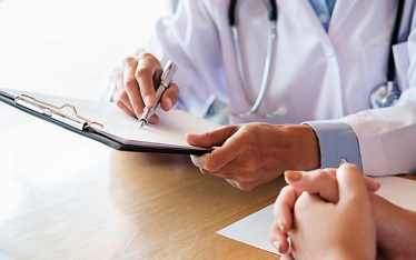 White male doctor holding a pen while pointing at a medical clip board on a wooden table