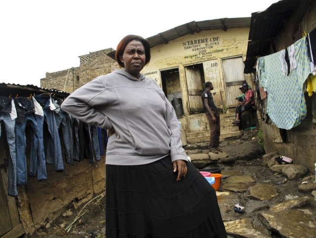 Slum mapper Emily Wangari stands outside a communal toilet in the Kiamutisya settlement of Mathare. This settlement has only four toilets for 4,000 residents. By mapping the problems, she hopes to pressure authorities to bring in more necessary services. Gregory Warner/NPR
