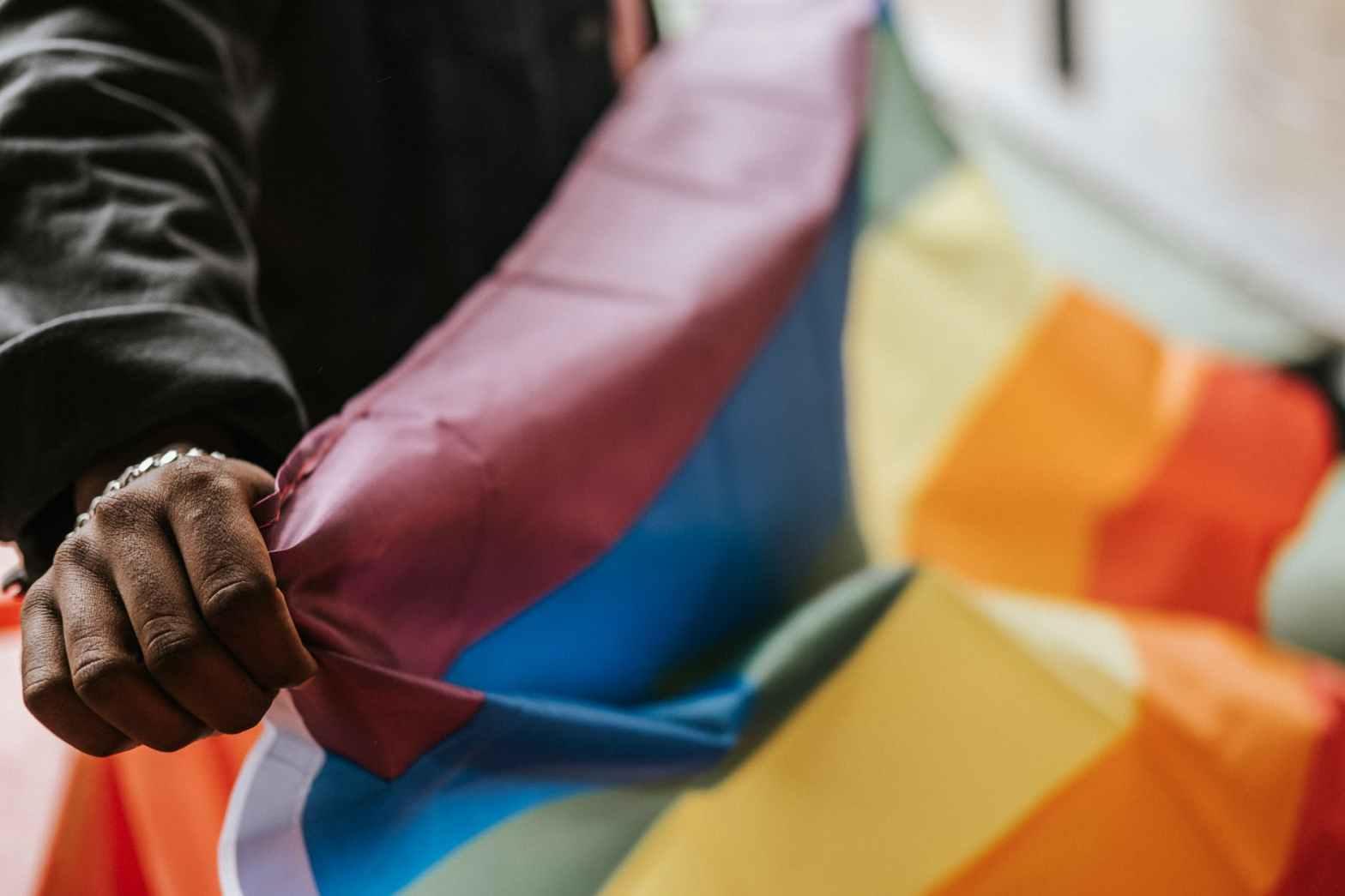 crop unrecognizable black gay demonstrating lgbt flag