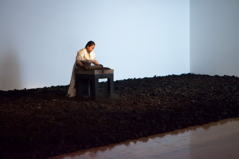 Melati Suryodarmo performs I'm a ghost in my own house 2012, a 12 hour durational work in which she crushes hundreds of kilograms of charcoal as a transformative and symbolic act of life's energy. / Image courtesy of QAGOMA