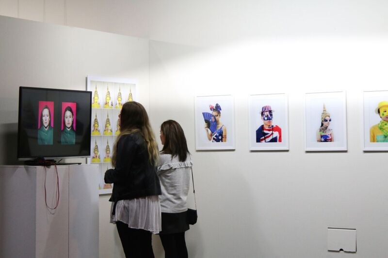 Viewers admiring art at Cause & Effect. Image credit: Carnival of the Bold.