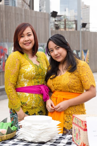 Two women in kebaya standing at a snack table, smiling.
