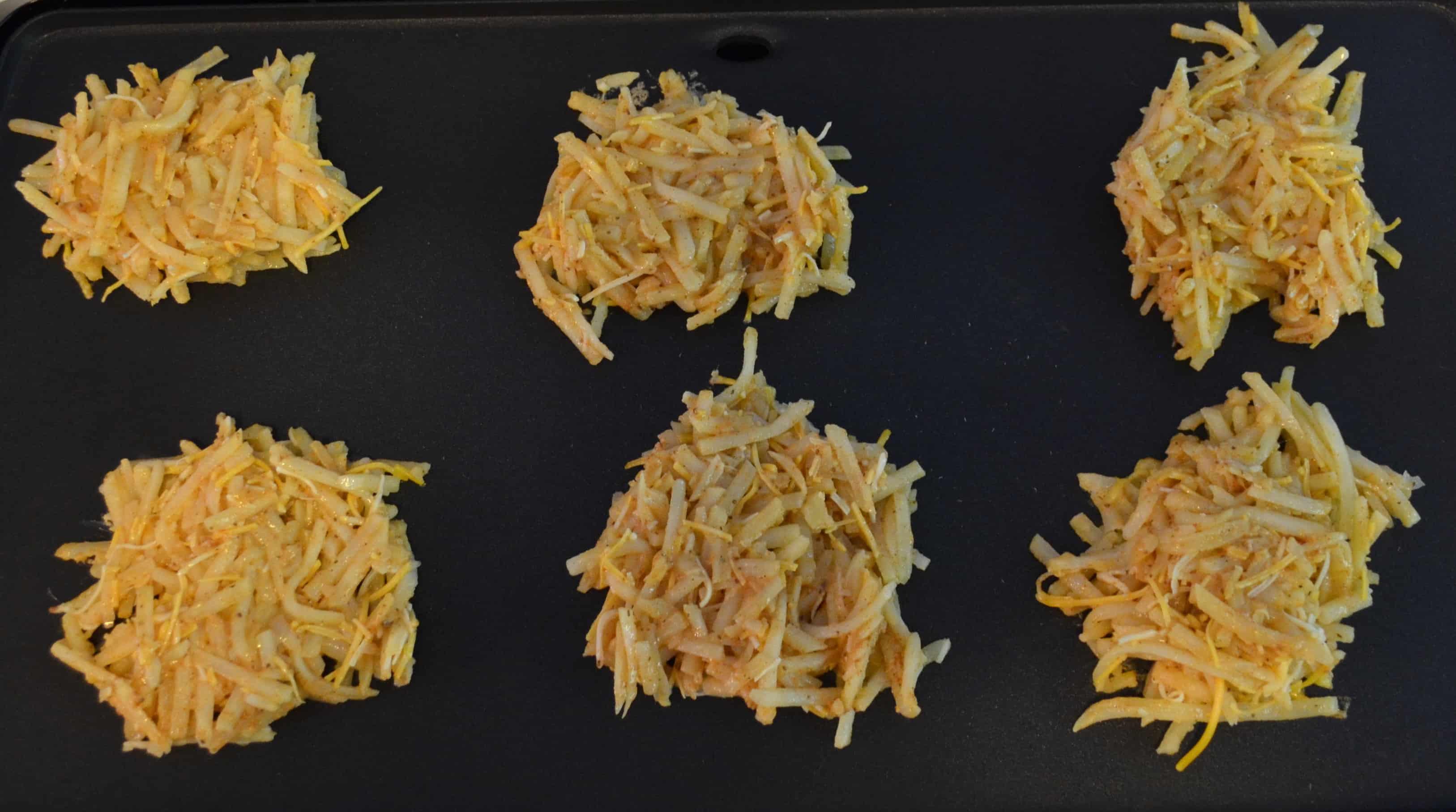 six potato pancakes on a griddle