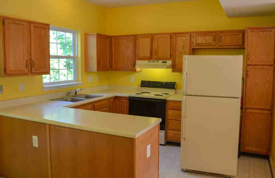 a yellow kitchen with orange oak cabinets