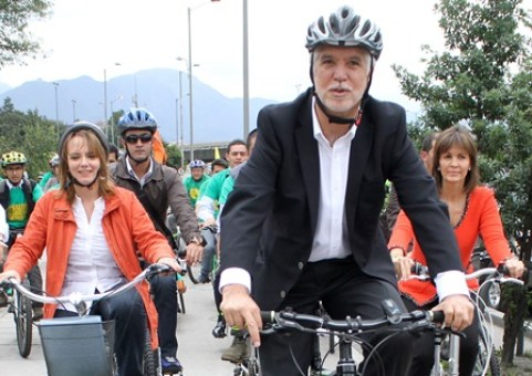 Colombian presidential candidate for the Green Alliance movement, former Bogota's mayor Enrique Penalosa (C), accompanied by his vice presidential partner Isabel Segovia (L), arrive bicycling to register their candidacy for the May 25 presidential election, in Bogota on March 26, 2014. Peñalosa, elected on March 9 as a candidate of the Green Alliance in the inner query of this political movemnt, would be the opponent of president and candidate for reelection Juan Manuel Santos in a possible runoff in Colombia, according to the polls. AFP PHOTO/Felipe Caicedo