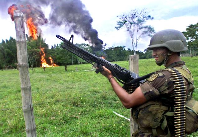 PUERTO ASIS, COLOMBIA - FEBRUARY 12:  A Colombian Army soldiers stands guard as cocaine paste is destroyed by fire 12 February 2001 in Puerto Asis, Colombia, 863 kms (536 miles) south of Bogota. Official data from the 19 December 2000 beginning of Plan Colombia say 20,000 hectares of cocaine leaf have been eradicated.  (Photo credit should read RODRIGO ARANGUA/AFP/Getty Images)