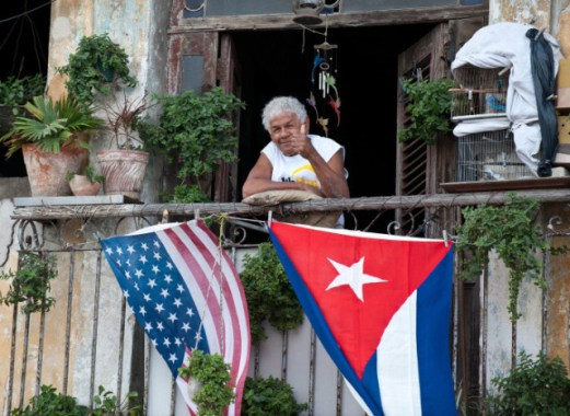 A Cuban gives the thumbs up from his balcony decorated with the US and Cuban flags in Havana, on January 16, 2015. The United States will ease travel and trade restrictions with Cuba on Friday, marking the first concrete steps towards restoring normal ties with the Cold War-era foe since announcing a historic rapprochement. AFP PHOTO/YAMIL Lage