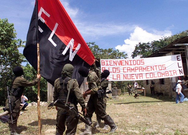 """Members of the National Liberation Army (ELN) set the organization's flag in San Francisco, a mountainous region in northern Colombia, where representatives of the government met with rebel leaders , Monday, Oct. 12, 1998. After the meeting the participants announced the call for a forum to meet February discuss peace prospects. With an estimated 5,000 fighters, the ELN is the country's second-largest guerrilla movement. The sign in the back reads """"Welcome to the camps for the new Colombia."""" (AP Photo/Fernando Llano)"""