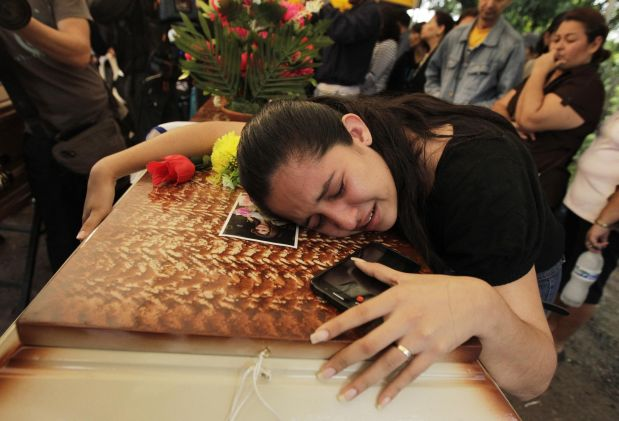 A friend lies over the coffin of Maria Jose Alvarado during a wake for Maria Jose and her sister Sofia outside their home in Santa Barbara November 20, 2014. The Honduran beauty queen has been found shot dead in a suspected crime of passion just days before she was due to compete in the Miss World pageant in London, police said on Wednesday. The bodies of Maria Jose, 19, and her sister Sofia, 23, were found buried near a river in the mountainous region of Santa Barbara in western Honduras, said Leandro Osorio, head of the criminal investigation unit. REUTERS/Jorge Cabrera (HONDURAS - Tags: CRIME LAW CIVIL UNREST ENTERTAINMENT)