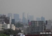 Panorama aéreo de un barrio sureño de la Ciudad de México con sus edificios semiocultos por la polución. Crédito: Emilio Godoy/IPS.