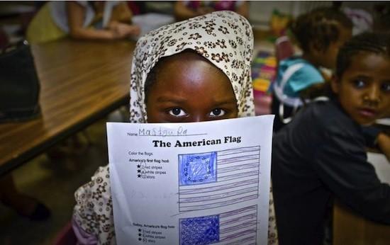 Mastoura Hasan, de siete años, refugiada sudanesa reasentada en Louisville, Kentucky, muestra con orgullo su dibujo de la bandera de la Unión durante una clase de cultura americana. Mastoura huyó de Sudán con su padre, su madre y tres hermanos en medio de intensos combates. Llegaron a Estados Unidos el pasado mes de diciembre.