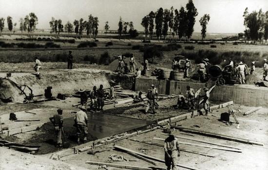Año 1945. Obras en el canal de los Presos, en el Río Guadalquivir. Al fondo, de oscuro, se aprecia la silueta de un Guardia Civil.