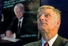 Franklin Graham. Tras él, cartel con la imagen de su padre, Billy Graham
