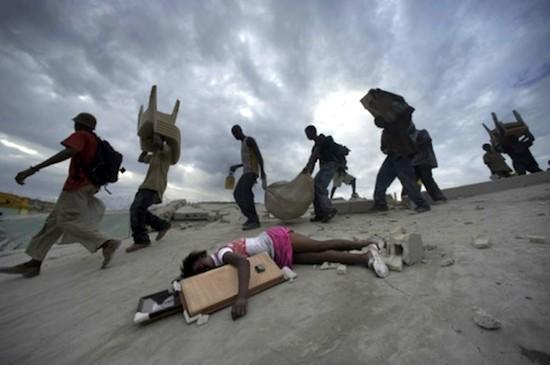 © Lucas Oleniuk. La niña Fabienne Cherisma, de 14 años, yace muerta en Haití en el terremoto que asoló el país mientras saqueadores pasan de largo a su lado con sus botines