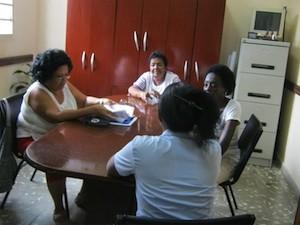 Miriam Fernández, de espaldas, conversa con especialistas del Taller de Transformación Integral del Barrio de Pogolotti, en el oeste de La Habana. Crédito: Patricia Grogg/IPS