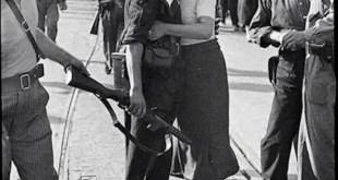 Foto: Agustí Centelles, Archivos Estatales MECyD, Centro Documental de la Memoria Histórica. Una joven besa a Joan García Oliver (1901-1980), dirigente sindicalista de la columna de Los Aguiluchos, durante el desfile de despedida hacia la estación del Norte, en Barcelona. 28 de agosto de 1936. '[Todo] Centelles, 1934-1939'. Instituto Cervantes, Madrid, 2014