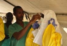 Miembros del equipo de MSF en Guinea poniéndose el traje protector antes de entrar al hospital. © Amandine