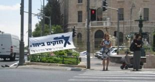 """Cartel belicista en Jerusalén con la leyenda """"Fuertes juntos, amamos a Israel y confiamos en el ejército"""". Crédito: Pierre Klochendler/IPS"""