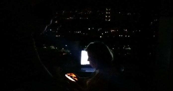 Algunas luces en barrios lejanos, a los que ya había llegado la electricidad, y algo de batería en los dispositivos animan la búsqueda de información sobre los familiares distantes en un hogar de Colinas de Santa Mónica, en una colina de Caracas, durante el inédito apagón de Venezuela. Crédito: Humberto Márquez/IPS