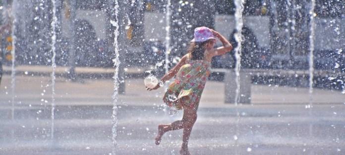 WMO/OMM: Una niña juega en unas fuentes para aliviar el calor del verano