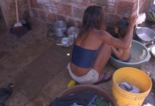 UNICEF/Versiani: Susana, de 14 años, baña a su pequeño sobrino detrás de su vivienda en un barrio pobre de una gran ciudad brasileña. La pobreza y la desigualdad obstaculizan el desarrollo social y sostenible en América Latina.