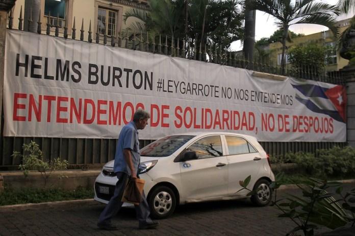 Una pancarta contra la Ley Helms Burton, una norma con la que se busca forzar que otros países participen en el embargo comercial, económico y financiero de Estados Unidos contra Cuba, destaca en la fachada del Instituto cubano de Amistad con los Pueblos, en La Habana. Crédito: Jorge Luis Baños/IPS