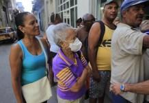 Sonia Gálvez, de 87 años y entre el grupo de mayor riesgo de contagio del coronavirus, se protege con una mascarilla mientras espera para comprar algunos medicamentos en una farmacia de La Habana, en Cuba. Foto: Jorge Luis Baños/IPS