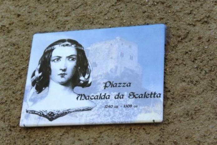Placa de la plaza Macalda de Scaletta junto a un dibujo de su figura, al lado del castillo de su localidad natal
