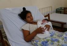Una madre adolescente con su bebe recién nacido en brazos, en una sala del hospital materno de la ciudad de Camagüey, en el centro de Cuba. Los matrimonios y uniones antes de los 18 años son identificados por UNFPA en su nuevo informe como la práctica nociva contra el desarrollo de las niñas que más preocupa en América Latina y El Caribe. © Jorge Luis Baños/IPS