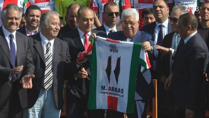 El presidente de la ANP, Mahmud Abbas, exhibe la camiseta que le regalaron durante su visita al club en 2018