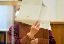 Eyad al Gharib, torturador sirio, intenta cubrirse el rostro en la sala del tribunal