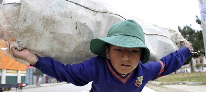 """Un niño carga un saco con botellas de plástico en La Paz. La OIT considera que en 2021 se debe """"pisar el acelerador"""" para erradicar el trabajo infantil en América Latina y el Caribe. Foto: Marcel Crozet/OIT"""