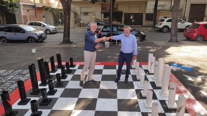 El ajedrecista alemán Dirk Maxion, a la izquierda, saluda al alcalde de Avezzano, Giovanni Di Pangrazio en el tablero.