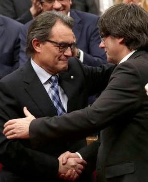 Artur Mas y Carles Puigdemont se saludan tras el pleno de investidura de nuevo presidente de la Generalitat