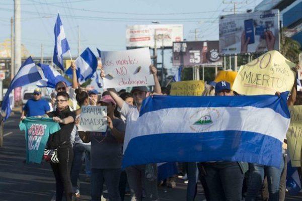 Residentes en Managua, apostados en la céntrica avenida de Metrocentro, ondean banderas nicaragüenses, durante la manifestación el lunes 23 de abril contra el gobierno de Daniel Ortega. Crédito: Jader Flores/IPS