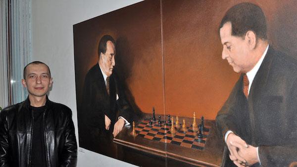 Roman Gumanyuk ante el retrato de Alekhine y Capablanca que disputaron el campeonato del mundo en Buenos Aires en 1927.