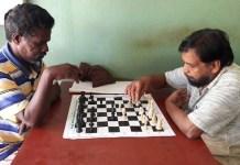 C. Unnikrishnan –-derecha- juega una partida con un vecino de Marottichal.
