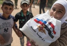 Niños de Alepo reciben la ayuda humanitaria procedente de Armenia aunque luzca la bandera rusa.