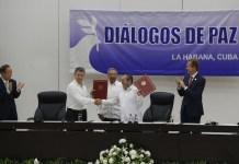El presidente de Colombia, Juan Manuel Santos (izquierda), y Rodrigo Londoño, Timochenko, máximo comandante de las Fuerzas Armadas Revolucionarias de Colombia (FARC), se dan un apretón de manos mientras blanden el histórico acuerdo, que firmaron este 23 de junio en La Habana y que pone fin a la guerra en Colombia. Crédito: Jorge Luis Baños/IPS