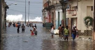 Residentes de La Habana transitan por una calle vecina al malecón de la capital de Cuba, inundada por la embestida del mar tras el paso del huracán Irma. Crédito: Jorge Luis Baños/IPS