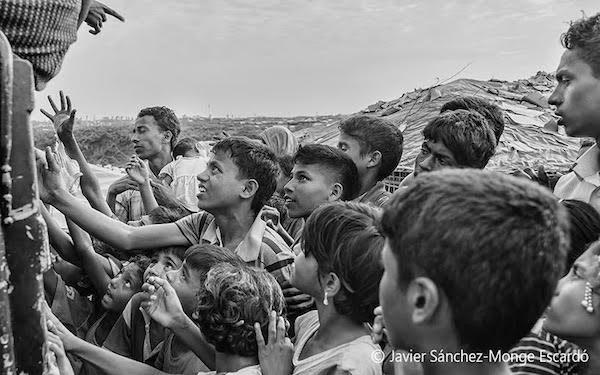 13/NOV/2017. Campo de refugiados de Kutupalung2: Reparto de alimentos Día tras día, la mayoría de los refugiados se ven obligados a aguardar largas colas o a apelotonarse desordenadamente junto a los repartidores de víveres, hasta poder hacerse con lo necesario para ellos y sus familias. A menudo los niños intentan escabullirse entre el gentío para poder llegar a estar en primera línea, y muchos hacen por llamar la atención de los repartidores lo antes posible. La mayor parte de su comida diaria consiste en arroz blanco, que preparan tras haberlo cocinado en pequeñas hogueras hechas con trocitos de madera que buscan en las cercanías del campo de refugiados.