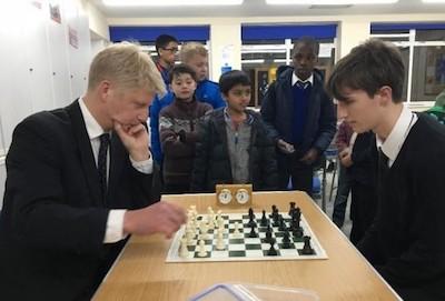 El entonces ministro Jo Johnson juega ante el alumno Edwin