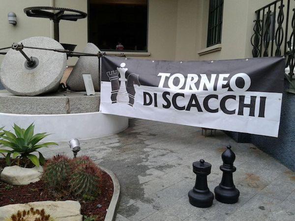 Pancarta del torneo de ajedrez en el Museo del Olivo de Imperia, donde se observa una muela de molino de almazara.