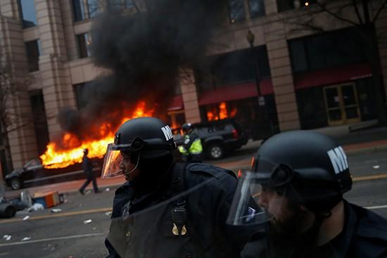 Policias antidisturbios delante de una limusina incendiada en el centro de Washington. CPJ/ Reuters/ Adrees Latif
