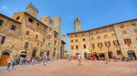 San Gimignano, Italy - July 3, 2018: Panoramic view of famous Piazza della Cisterna in the historic town of San Gimignano on a sunny day, Tuscany, Italy