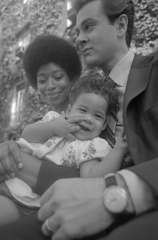 """12 Aug 1970, New York, New York, USA --- While talking about her book, Alice Walker seems content to let her daughter, Rebecca, 8 1/2 months, steal the spotlight. Alice's husband, Mel Leventhal, does the """"baby-sitting."""" --- Image by © Bettmann/CORBIS"""